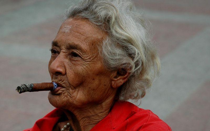 Пожилая женщина курит